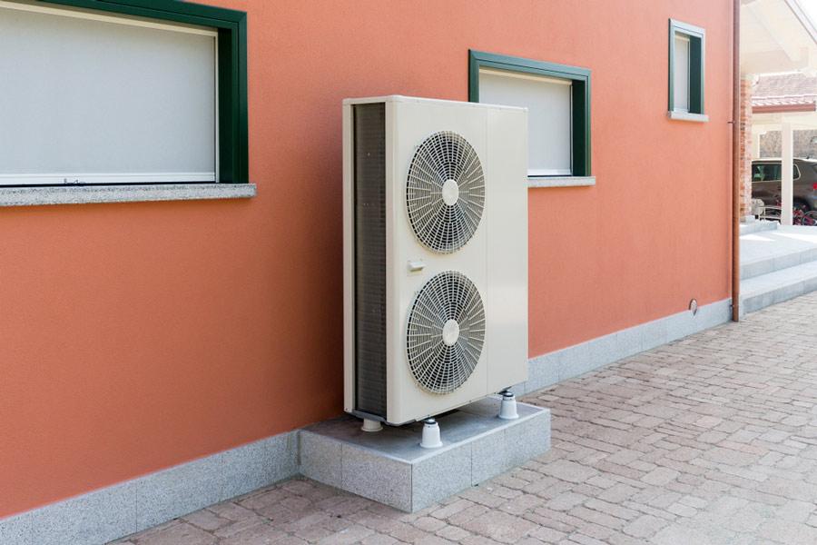 Jednostka zewnętrzna powietrznej pompy ciepła ustawiona na tyłach budynku - otwartaenergia.pl